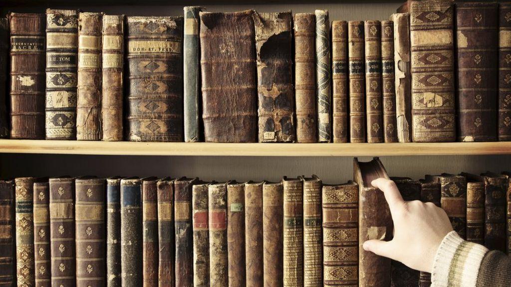 bookshelf hand removing book